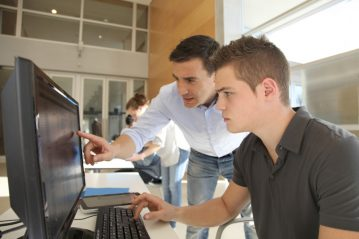 Teacher and student working on computer