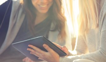Close up of 2 girls looking at a digital tablet outdoors