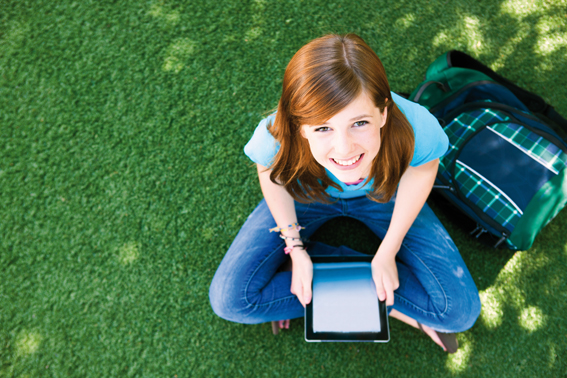 Overhead shot of a beautiful young red-headed girl on the grass with a backpack and a digital tablet